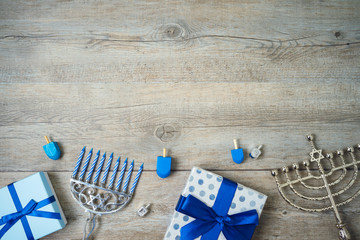 Jewish holiday Hanukkah background with menorah, gift boxes and dreidel on wooden table.