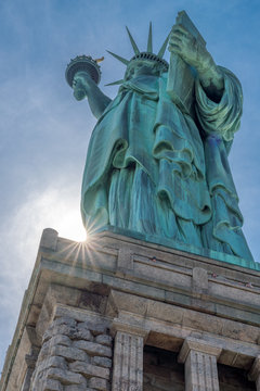 Statue of Liberty with sunburst. Image of the Statue of Liberty shot from a unique angle: looking up and timed so that a partially obscured sun makes a starburst at the base of the pedestal.