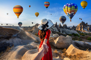 Wall Mural - Women tourists holding man's hand and leading him to hot air balloons in Cappadocia, Turkey.