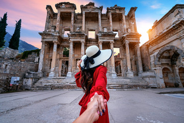 Women tourists holding man's hand and leading him to Celsus Library at Ephesus ancient city in Izmir, Turkey..