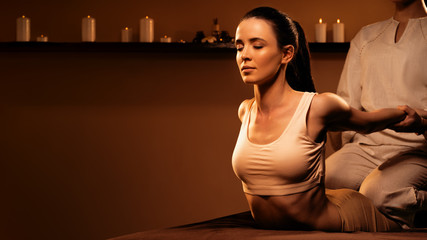 Young pretty woman has Thai massage at luxury spa. Warm inviting colors, calm atmosphere, charming light.