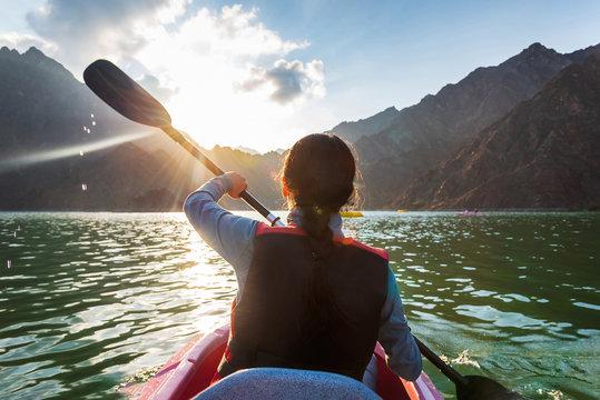 Woman kayaking in a lake at sunset