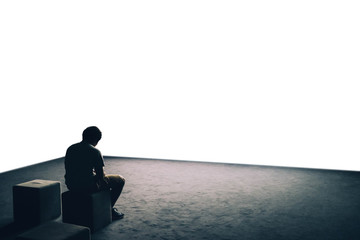 Solitary depressed sad man person boy sitting by himself on his own alone seated head bowed down. Blank white copy space. Mental health depression stress anxiety wellbeing wellness background backdrop