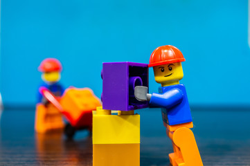 Lego construction worker building something with plastic bricks on December 14, 2019 in Poznan, Poland.