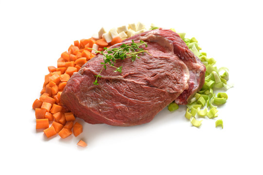 Piece of raw beef meat with vegetable ingredients like carrots, leeks and celery, isolated on a white background, copy space