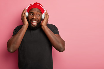 Indoor shot of cheerful bearded man listens radio broadcast, uses headphones, wears red hat and black t shirt, looks gladfully aside, spends free time with music, isolated on pink background Fotobehang