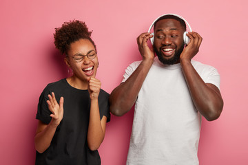Joyful curly haired woman pretends singing in microphone plump bearded man listens music in headphones, have broad smiles, enjoy favourite playlist, relax after hard working week. People and rest Fotobehang