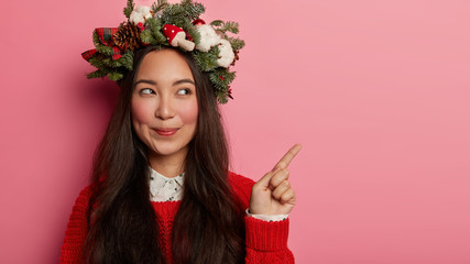 Horizontal shot of attractive brunette woman wears holiday wreath, points fore finger on right side, demonstrates promo, wears Christmas wreath made of spruce, has appaeling look, isolated on pink