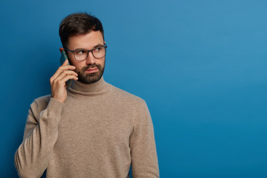 Photo of serious bearded young guy talks on phone, calls someone via modern gadget, expresses seriousness, has important call, wears casual brown jumper, looks aside thoughtfully, gazes right
