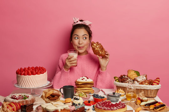 Addicted young Asian female drinks milk and eats delicious croissant, licks lips from pleasant taste, enjoys desirable favourite dessert, sits at table with many sweet products, isolated on pink wall