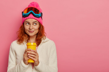Poster Glisse hiver Beautiful thoughtful redhead girl stands with takeaway coffee in hands, wears snowboarding goggles, spends winter holidays in mountains, thinks about something, models over rosy wall. Extreme sport