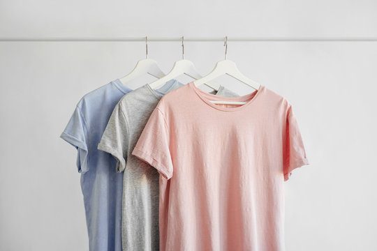 T-Shirts in pastel color on hanger on white background. Basic female clothes. Spring/summer outfit.