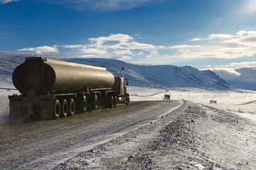 Tankers and trucks driving the Dalton Highway through the Brooks Range mountains Alaska