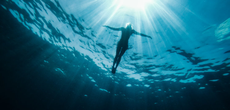 Woman floating in the sea and rays of light piercing through