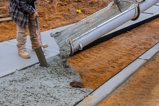 Truck loads of concrete poured into the concrete at a construction in a sidewalk