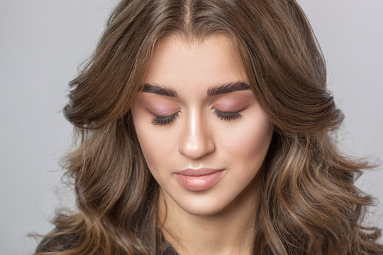 Portrait of a beautiful happy woman with long eyelashes, beautiful fresh nude make-up, thick eyebrows and with clean skin in a beauty salon. Eyelash extensions. Face close-up. Make-up concept