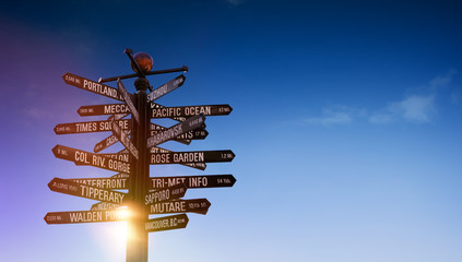 World Traffic signs and directional signpost pointing to famous travel destinations with blue cloudy sky and free copy space for text on the right