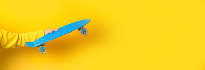 Wall Mural - hand holding blue skate board over yellow background, panoramic mock up image