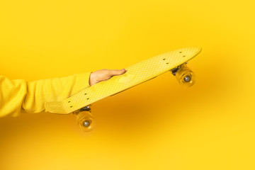 Wall Mural - hand holding yellow  skate board over yellow background,