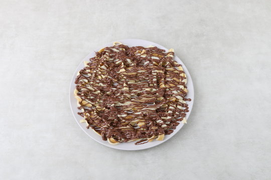 crepe with chocolate sauce and nutella pistachio  on white background