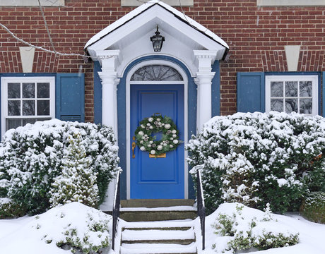 Front door of  house with Christmas wreath and snow covered pine bush