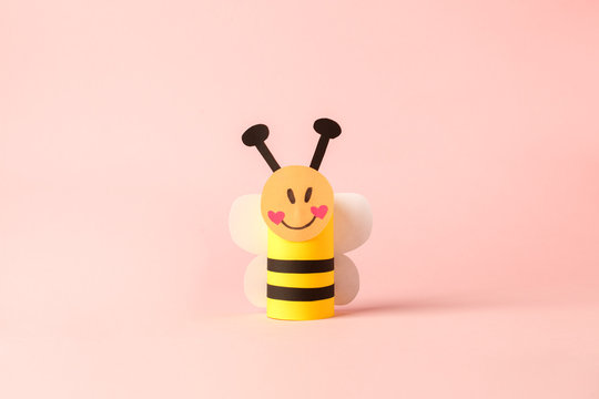 Paper bee for valentine, birthday, baby shower, daycare party. Easy craft for kids on blue background, simple diy idea from toilet rool tube, recycle concept, copy space