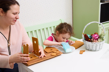 Mom glues the details gingerbread house with protein cream while her daughter looks. child tries icing cream from a pastry bag