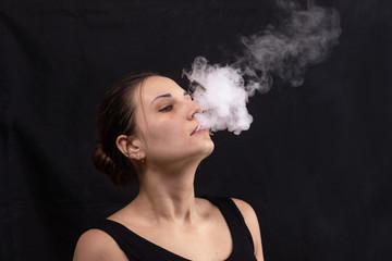 Portrait of girl blowing smoke water vapor from vape