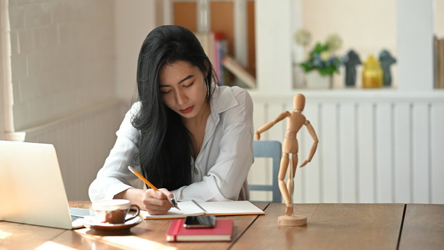 Asian female writing on notebook paper in home office workspace.