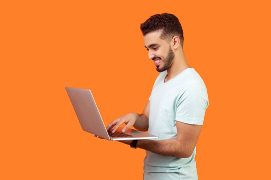 Side view portrait of cheerful brunette man with beard in white t-shirt working on laptop typing email or chatting in social network, happy face expression. studio shot isolated on orange background
