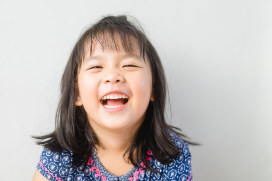 Happy Little asian girl child showing front teeth with big smile and laughing: Healthy happy funny smiling face young adorable lovely female kid.Joyful portrait of asian elementary school student.