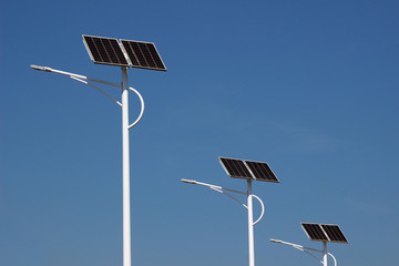 Row of three street lamp posts with solar powered energy panel against a clear blue sky background. Fotomurales