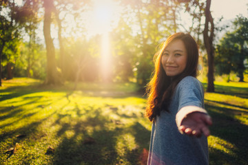 Fototapeten Gelb Follow me, a beautiful asian woman holding hands and leads into the park before sunset
