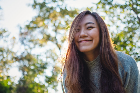 Portrait image of a beautiful asian woman standing among nature in the park