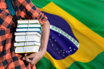Brazil national education concept. Close up of teenage student holding books under his arm with country flag background.