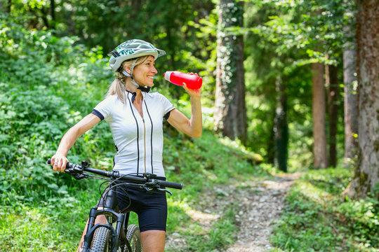 woman drinks from her water bottle on mountain bike