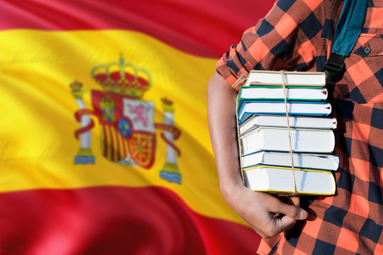 Spain national education concept. Close up of teenage student holding books under his arm with country flag background.