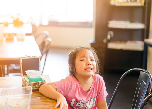 Angry, hungry,Crying little asian girl screaming in restaurant.Cry kid.Facial expression.Attention deficit hyperactivity disorder (ADHD) Concept.