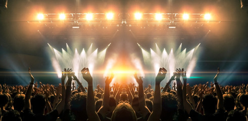 Photo of a concert hall with people silhouettes clapping in front of a big stage lit by spotlights. Shot is taken from concert crowd point of view, lens flare is visible. Fotobehang