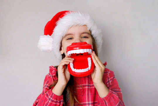 happy funny baby girl in red Christmas hat with toy model teeth on grey background.
