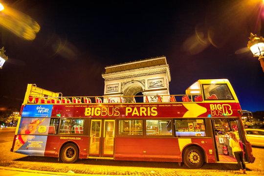 Paris, France - July 2, 2017: touristic bus at Champs Elysees with Arc de Triomphe at night in Paris on background. Hop-On Hop-Off Tour, Paris. Explore top Paris attractions. Night urban scene.