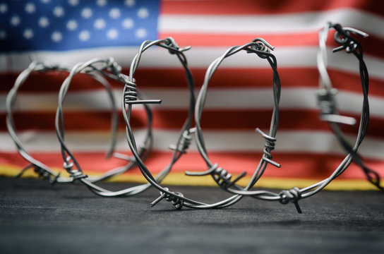 Barbed wire and United States of America flag , immigration stock photo.