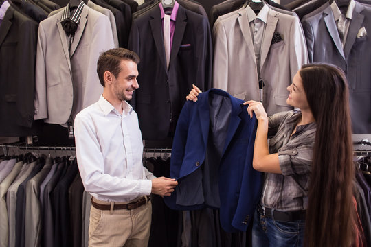 Girl seller helps to pick up a client in a jacket menswear boutique