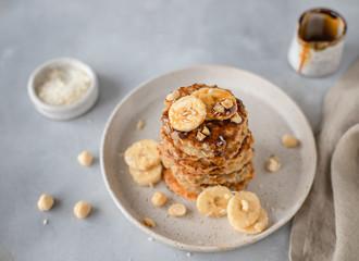 healthy oatmeal pancake with banana, hazelnut, syrup. gray concrete background, top view, horizontal image
