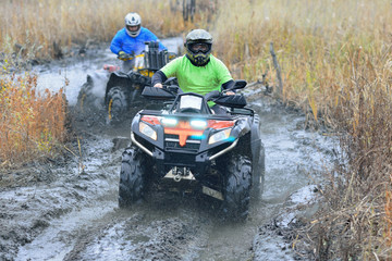 Cool picture of active ATV and UTV driving in mud and water at Autumn