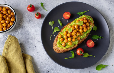avocado toast with roasted chickpeas, herbs, cherry on a dark plate. vegan snack. gray background, horizontal image