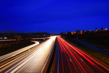 Lightpainting of a highway at night with road traffic. Spun from car headlights in long exposure mode. City in the background.