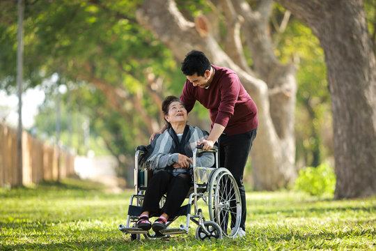 Asian senior woman on wheelchair with son