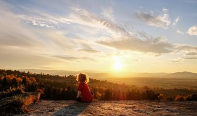 Foto auf Acrylglas Beige The boy enjoys the sunset in the mountains