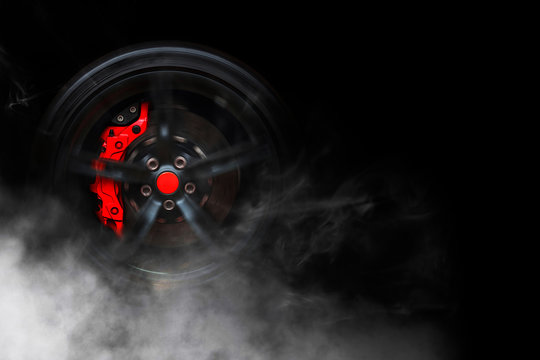Isolated generic sport car wheel with red breaks drifting and smoking on a black background